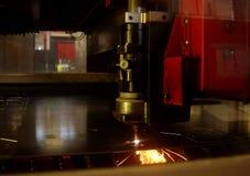 Laser-cutting av metallarket med sparks arkivfoto