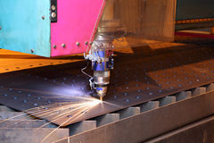 Laser cutting heads for vertical cutting sheets metal. Royalty Free Stock Photography