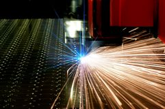 Laser cutting of metal sheet with sparks. Technical photo Stock Image