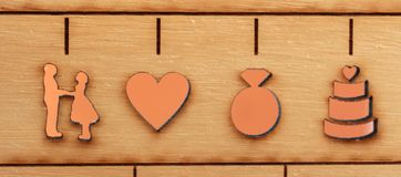 Laser engraved symbols of wedding, bride, groom, heart, ring and cake Royalty Free Stock Image
