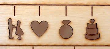 Laser engraved symbols of wedding, bride, groom, heart, ring and cake Stock Photos