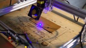 Laser engraving machine work. 4K. Laser burns on cow skin logo. Leather purse stock video