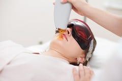 Laser-hårborttagning på framsidan för flicka` s Apparaturcosmetology Sp Arkivbilder