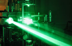 Laser laboratory. Green laser beam propagating in a research lab royalty free stock photo