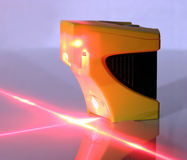 Laser Level. Lighted laser level.  Displaying perpendicular lines.  Image a bit dark to show the projected lines Stock Photos