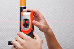 Laser level gage. Man hands measuring with laser level gage stock images