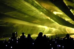 Laser party. Silhouetted crowd attending laser show. Streaks of light projected overhead Royalty Free Stock Photos