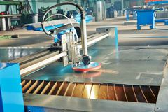Laser or plasma cutting of metal sheet with sparks. Industrial laser or plasma cutting processing manufacture technology of flat sheet metal steel material with Royalty Free Stock Image