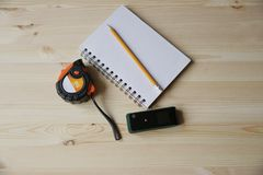 Laser range finder, tape measure, notebook, pencil on a light background royalty free stock image