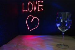 Laser rysujący miłość znak dla tła z glassful bąbla napój dla przyjęcia i świętowania valentines dzień zdjęcia stock