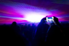 Laser show party rays in front of smartphone filming video. Best visual show with a crowd silhouette and great laser rays for e.g. an illustration background of Stock Photo