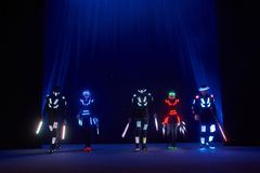 Laser show performance, dancers in led suits with LED lamp, very beautiful night club performance, party.  Royalty Free Stock Image