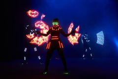 Laser show performance, dancers in led suits with LED lamp, very beautiful night club performance, party.  Royalty Free Stock Images