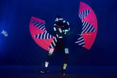 Laser show performance, dancers in led suits with LED lamp, very beautiful night club performance, party.  Stock Images
