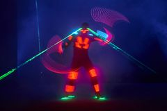 Laser show performance, dancers in led suits with LED lamp, very beautiful night club performance, party.  Stock Photo