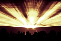 Laser show rays in fire red yellow and orange party colors. Best visual show with a crowd silhouette and great laser rays for e.g. an illustration background of Stock Images