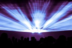 Laser show rays in nightlife party blue and purple colors. Best visual show with a crowd silhouette and great laser rays for e.g. an illustration background of Royalty Free Stock Photography
