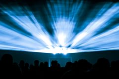 Laser show rays in nightlife party with shining blue colors. Best visual show with a crowd silhouette and great laser rays for e.g. an illustration background of Royalty Free Stock Images
