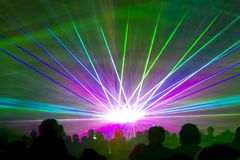 Laser show rays. Very colorful show with a crowd silhouette and great laser rays on pyrotechnic festival Royalty Free Stock Photo