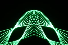 Laser Spirograph in green light expanded in a geometric shape. A spirograph made with a green led light in a geometric shape with leading lines going up royalty free stock photography