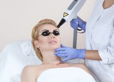Laser tattoo removal on woman`s eyebrows. In a beauty salon royalty free stock photo