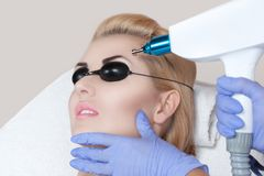 Laser tattoo removal on woman`s eyebrows. In a beauty salon royalty free stock image