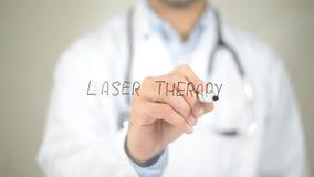 Laser-terapi, doktorshandstil på den genomskinliga skärmen arkivfoto