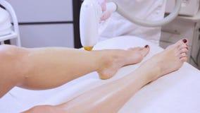 Laserepilation op benen van cliëntvrouw in kuuroordsalon, moderne technologieën in de kosmetiek stock footage