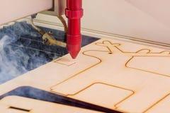 Lasergraveur die en houten raad met rook werken graveren stock afbeeldingen