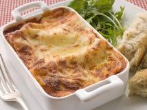 Lasgane com folhas da salada e pão italiano Fotos de Stock