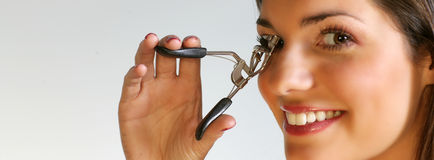 Lash curler. Close up picture of a pretty woman with a lash curler Royalty Free Stock Photography