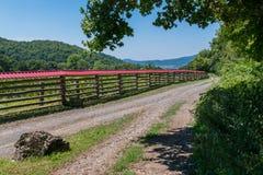Lasowa droga wzdłuż drewnianego ogrodzenia z czerwonym dachem przeciw tłu szerokie zielone góry zdjęcie royalty free