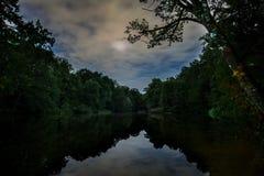 Lasowy jezioro odbija jaskrawe chmury obrazy stock