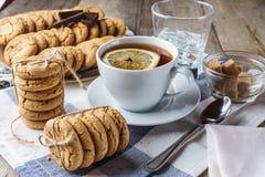 Lasque as cookies, um copo do chá com limão, açúcar, vidro do wate do gelo Fotos de Stock Royalty Free