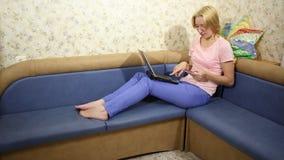 Lass сидя на софе дома и делает оплату товаров через интернет путем вход деталей их карточек банка видеоматериал