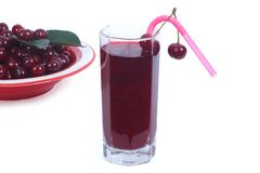 Lass of cherry juice isolated. Lass of cherry juice and plenty of ripe cherries isolated Stock Images