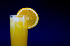 Lass of fresh orange juice with ice and a slice of orange isolated on a dark background. Lass of fresh orange juice with ice and a slice of orange isolated on a Stock Image