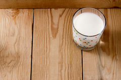 Lass of milk on a wooden background. Transparent glass of milk standing on a wooden surface Stock Photos