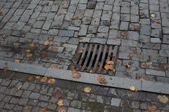 Lassen Sie auf der Straße ab, um Überschwemmung zu verhindern auf der Straße Grill der Wasserhoseabwasser-Abflussweise auf Straße Stockfotografie