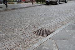 Lassen Sie auf der Straße ab, um Überschwemmung zu verhindern auf der Straße Ein Kanaldeckel in der Stadt, Herbst Lizenzfreie Stockbilder