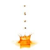 Lassen Sie das Fallen in orange Wasser mit dem Spritzen fallen, das auf Weiß lokalisiert wird Lizenzfreie Stockfotografie