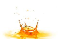 Lassen Sie das Fallen in orange Wasser mit dem Spritzen fallen, das auf Weiß lokalisiert wird Stockbild
