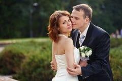 Lassen Sie mich Sie küssen - Bräutigamgriffe eine Braut in einem Park Lizenzfreie Stockbilder
