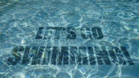 Lassen Sie uns den Text, zu schwimmen gehen, der unter Wasser in einem Swimmingpool erscheint lizenzfreie stockbilder