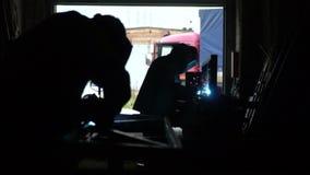 Lasser op het werk in de metaalindustrie Donkere ruimte Blauw licht en rook van lassen Langzame Motie stock video