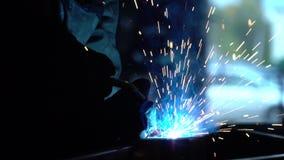 Lasser op het werk in de metaalindustrie Donkere ruimte Blauw licht en rook van lassen Lasser Langzame Motie stock video