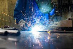 Lasser in zijn metaal van het workshoplassen stock afbeelding