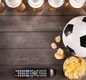 Lasses piwo z przekąską i piłki nożnej piłką kosmos kopii fotografia stock