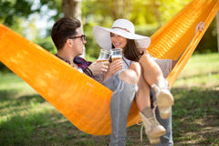 Lassie with boyfriend toast with glasses in hammock. Lovely lassie with boyfriend toast with glasses of beer in hammock in forest royalty free stock photo