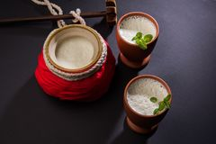 Lassie or lassi drink in terracotta glass. Lassie or lassi in terracotta glass - Lassi is an Authentic Indian cold drink made up of curd and milk and sugar Stock Photography